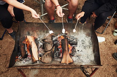 Buy stock photo Cropped shot of a group of friends toasting marshmallows around a campfire in nature