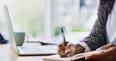 Buy stock photo Cropped shot of an unrecognizable woman making notes while sitting at her desk