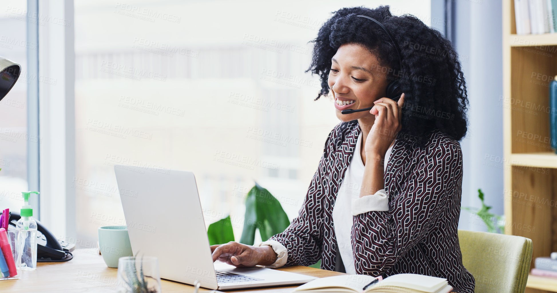 Buy stock photo Shot of a young businesswoman wearing a headset while using her laptop