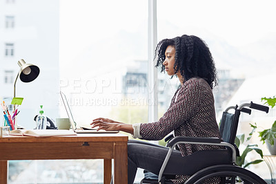 Buy stock photo Shot of a businesswoman sitting in her wheelchair while working on her laptop