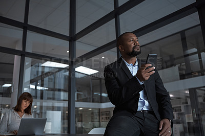 Buy stock photo Shot of a mature businessman using a cellphone while working with a colleague in an office at night