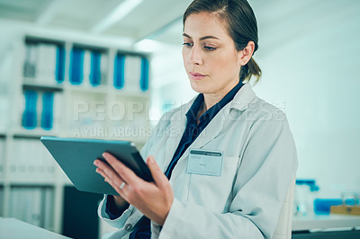 Buy stock photo Shot of a scientist using a digital tablet while conducting research in a laboratory