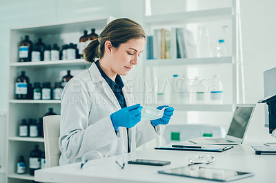 Buy stock photo Shot of a scientist putting on gloves and a face mask while working in a laboratory