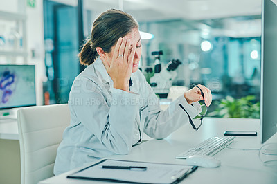 Buy stock photo Shot of a scientist experiencing stress while conducting research in a laboratory