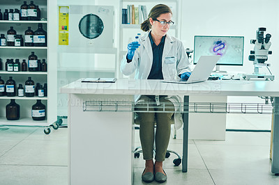 Buy stock photo Shot of a scientist using a laptop while conducting research in a laboratory