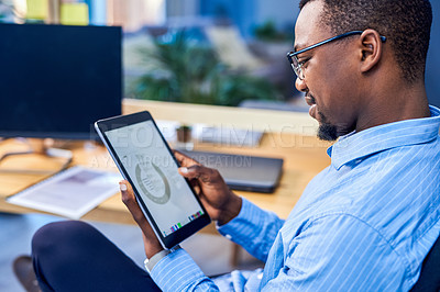 Buy stock photo Shot of a young businessman analysing graphs on a digital tablet in an office
