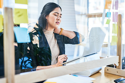 Buy stock photo Shot of a young businesswoman experiencing with neck pain while working on a laptop in an office