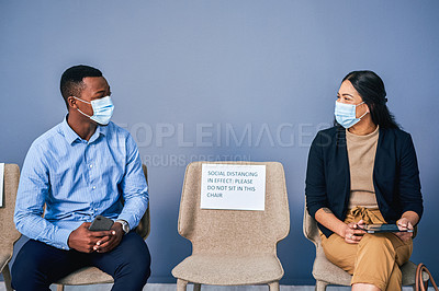 Buy stock photo Shot of two businesspeople wearing face masks while sitting in a waiting room