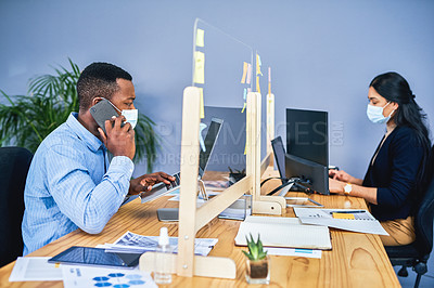 Buy stock photo Shot of a young businessman talking on a cellphone while working on a laptop in an office with a colleague in the background