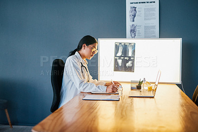 Buy stock photo Shot of a young doctor using a laptop while analysing an x ray in a modern hospital
