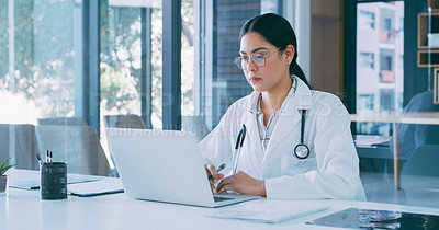 Buy stock photo Shot of a young doctor using a laptop in a modern hospital