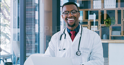Buy stock photo Portrait of a young doctor using a laptop in a modern hospital