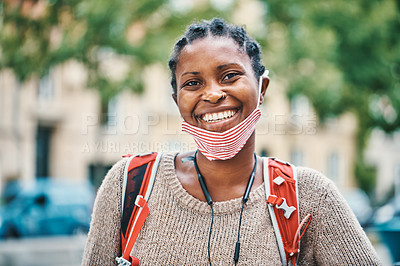 Buy stock photo Shot of a young woman wearing a face mask in the city