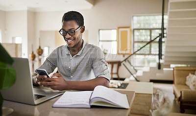 Buy stock photo Shot of a young man using a cellphone while working from home