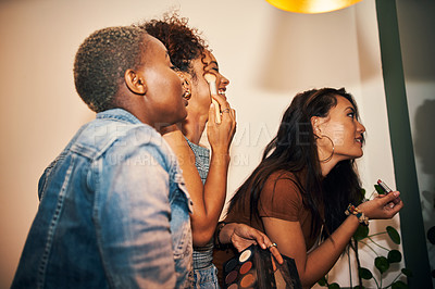 Buy stock photo Cropped shot of three friends doing their makeup together in the mirror at home
