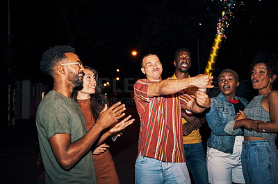 Buy stock photo Cropped shot of a group of friends using a confetti popper while out partying at night