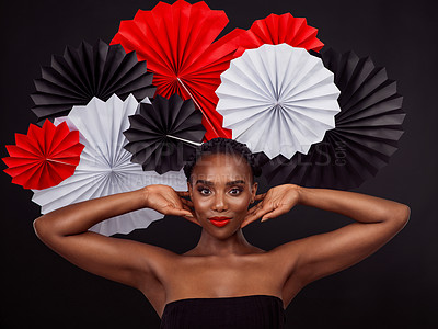 Buy stock photo Studio shot of a beautiful young woman posing with a origami fans against a black background