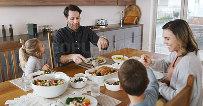 Buy stock photo Shot of a young family sharing a delicious meal together at home