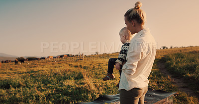 Buy stock photo Shot of a woman holding her baby girl while watching the animals on their farm