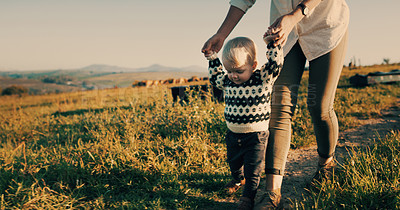 Buy stock photo Shot of an adorable baby girl learning to walk with her mother on their farm