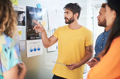 Buy stock photo Shot of a group of young businesspeople meeting to create a fitness plan in a modern office