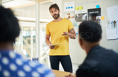 Buy stock photo Shot of a young businessman using a digital tablet during a presentation in a modern office