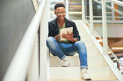 Buy stock photo Shot of a young businessman using a digital tablet on the stairs of a modern office