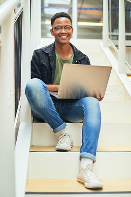 Buy stock photo Shot of a young businessman using a laptop on the stairs of a modern office