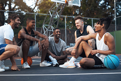 Buy stock photo Shot of a group of sporty young men chatting to each other on a basketball court