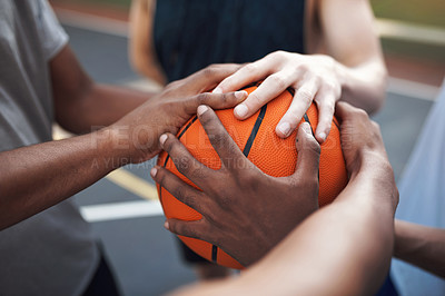 Buy stock photo Closeup shot of a group of sporty young men huddled around a basketball on a sports court