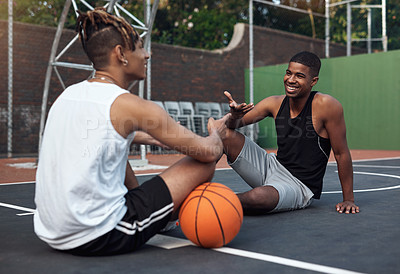 Buy stock photo Shot of two sporty young men chatting to each other on a basketball court