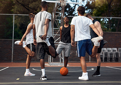 Buy stock photo Shot of a group of sporty young men stretching their legs on a basketball court