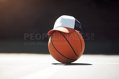 Buy stock photo Still life shot of a hat placed on top of a basketball in a sports court
