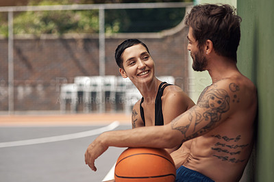 Buy stock photo Shot of two sporty young people taking a break after a game of basketball