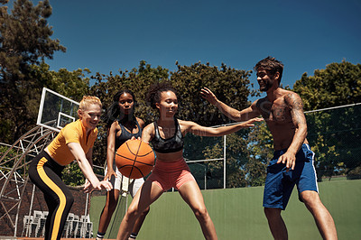 Buy stock photo Shot of a group of sporty young people playing basketball on a sports court