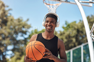 Buy stock photo Shot of a sporty young man listening to music while playing basketball on a sports court