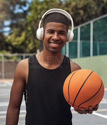 Buy stock photo Portrait of a sporty young man listening to music while playing basketball on a sports court