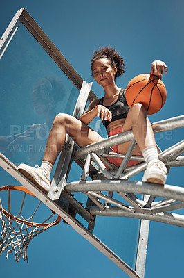 Buy stock photo Portrait of a sporty young woman sitting on a basketball hoop on a sports court