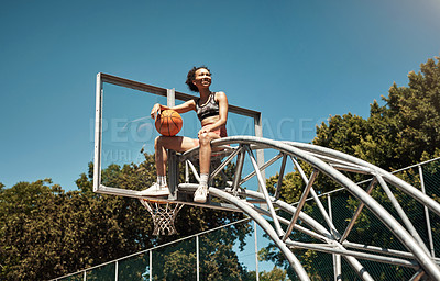 Buy stock photo Shot of a sporty young woman sitting on a basketball hoop on a sports court