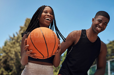 Buy stock photo Shot of two sporty young people playing basketball on a sports court