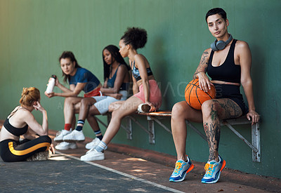 Buy stock photo Full length portrait of an attractive young female athlete sitting on a bench at the basketball court with her teammates in the background