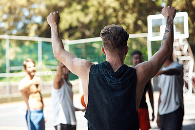 Buy stock photo Rearview shot of a sporty young man cheering with his friends on a sports court