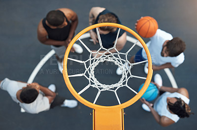 Buy stock photo High angle shot of a group of sporty young men hanging out on a basketball court