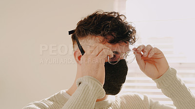 Buy stock photo Shot of a young man putting on a face mask at home