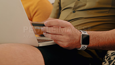 Buy stock photo Shot of a couple using a credit card and laptop on the sofa at home