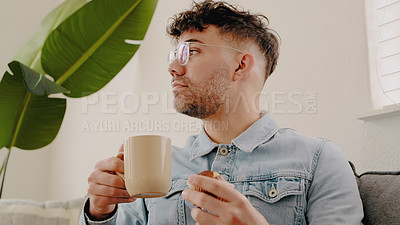 Buy stock photo Shot of a young man having coffee and a muffin while relaxing on the sofa at home