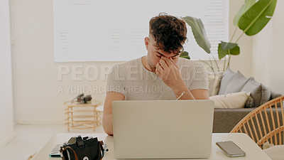 Buy stock photo Shot of a young man feeling stressed while working on a photography project at home