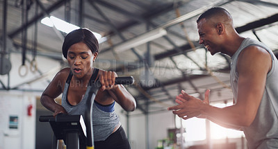 Buy stock photo Shot of a young woman working out on an exercise bike with her trainer in a gym