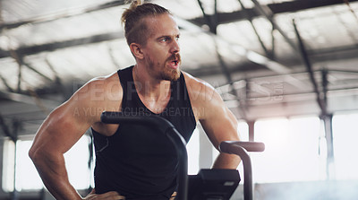 Buy stock photo Shot of a young man taking a break while working out on an exercise bike in a gym