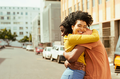 Buy stock photo Cropped shot of a young couple sharing a hug while out in the city